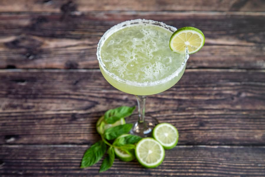 Margarita cocktail with lime wheels and mint