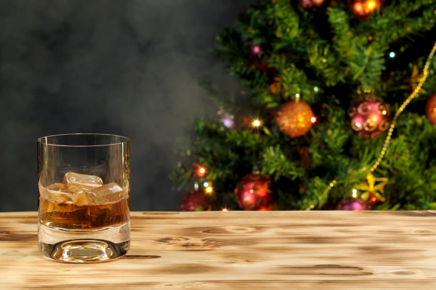 Glass of brandy on table next to Christmas tree