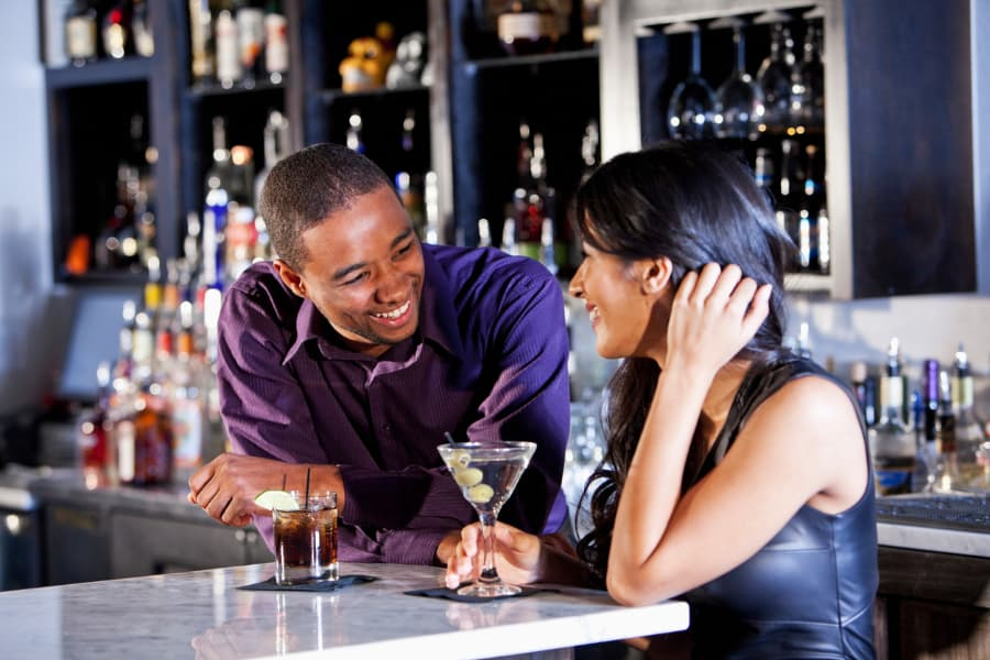 Couple sitting at bar enjoying cocktails together