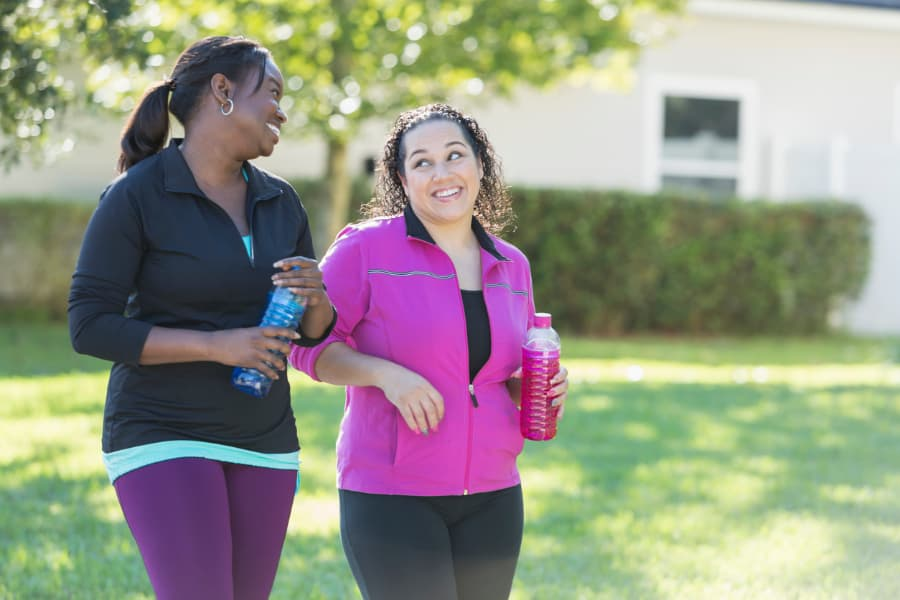 Two Women Walking With Energy Drinks