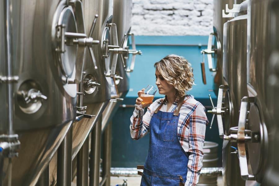 Woman Examining Beer Sample In Brewery